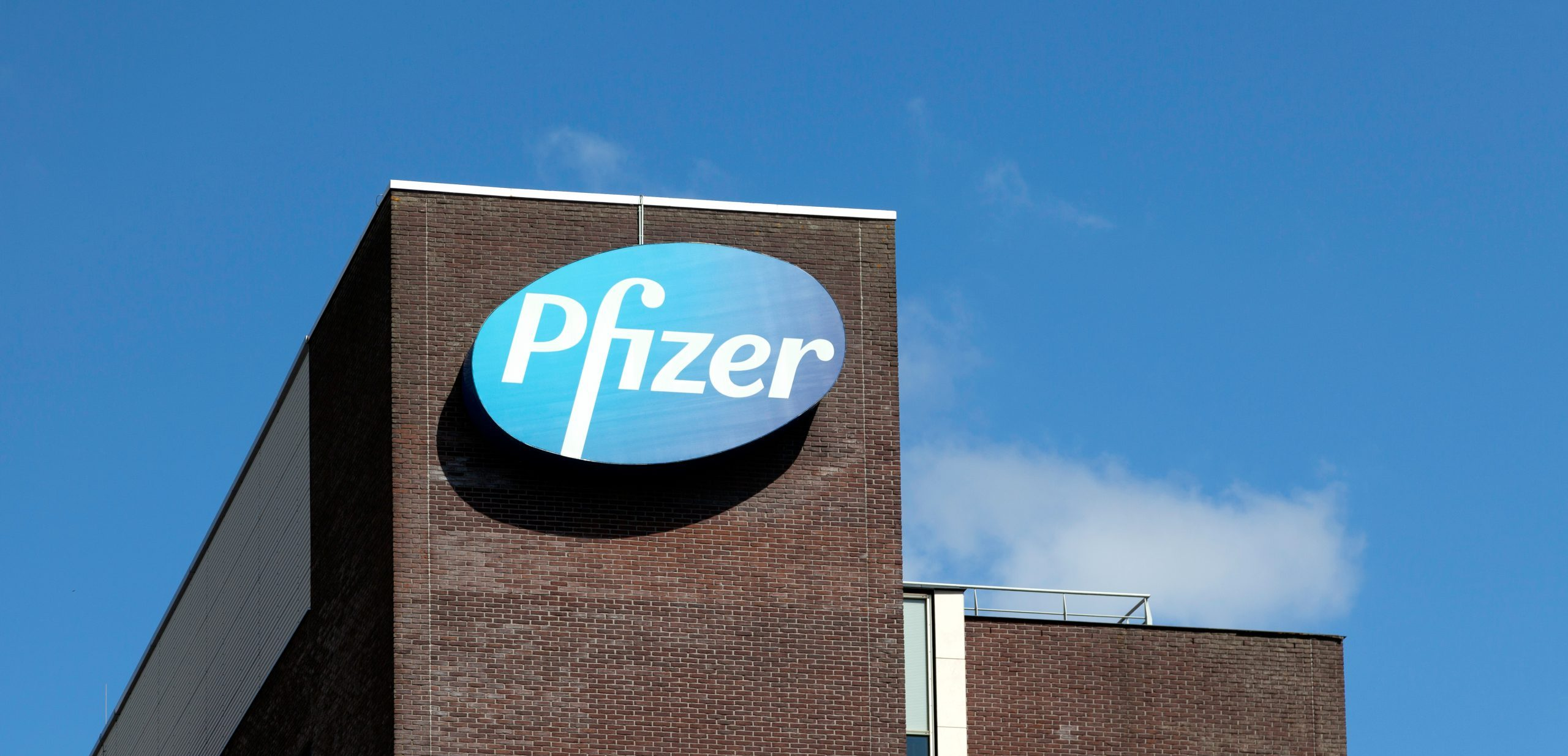 """Close up shot of the """"Pfizer"""" office building with the logo on the side, against a blue sky with white clouds."""
